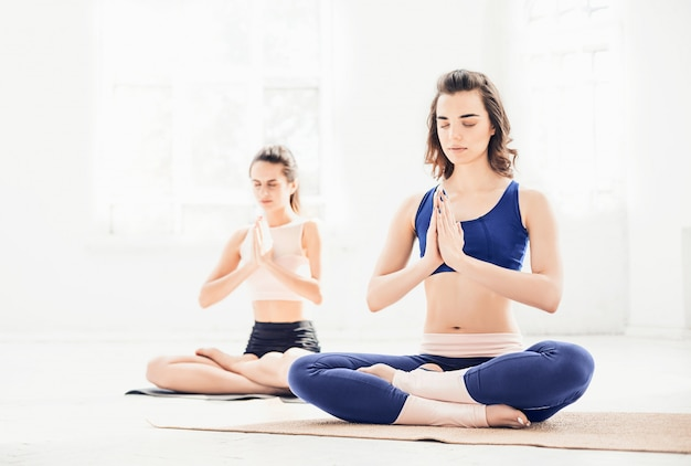Studio shot di giovani donne che fanno esercizi di yoga su bianco