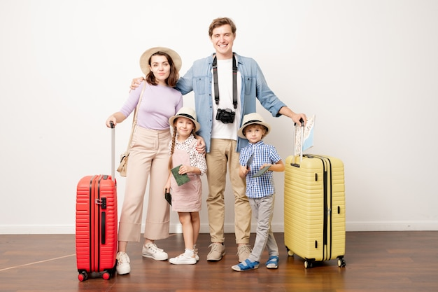 Studio shot di una giovane famiglia di quattro persone in abbigliamento casual in piedi in isolamento mentre si va a viaggiare in treno o in aereo