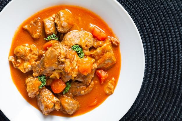 Stufato classico francese del vitello di concetto di alimento marengo de veau in piatto ceramico bianco con lo spazio della copia