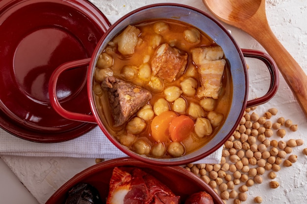 Stufato di ceci fatto in casa madrid stufato di ceci, carne e verdure (salsiccia, sanguinaccio, prosciutto, aglio, cipolla, carota, vitello, pollo). piatto tipico spagnolo