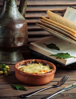 Stufato di cibo all'interno di una ciotola di terracotta ricoperta di formaggio fuso sulla parte superiore