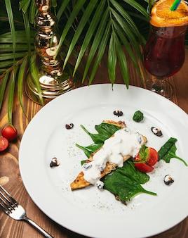 Stufato di pesce in salsa cremosa, pomodoro, prezzemolo sul piatto, coltello, forchetta in legno chiaro