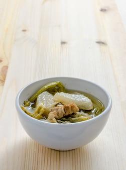 Stufato di verdure cinese, miscela di verdure e carne di maiale su fondo di legno