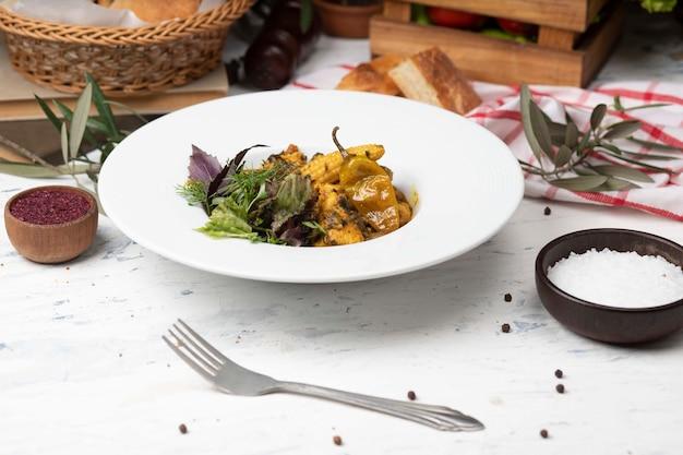 Stufato di verdure con carne, pezzi di mais, peperoncino e verdure, basilico, prezzemolo in piastra bianca.