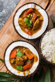 Stufato e riso nella vista superiore dei piatti della noce di cocco