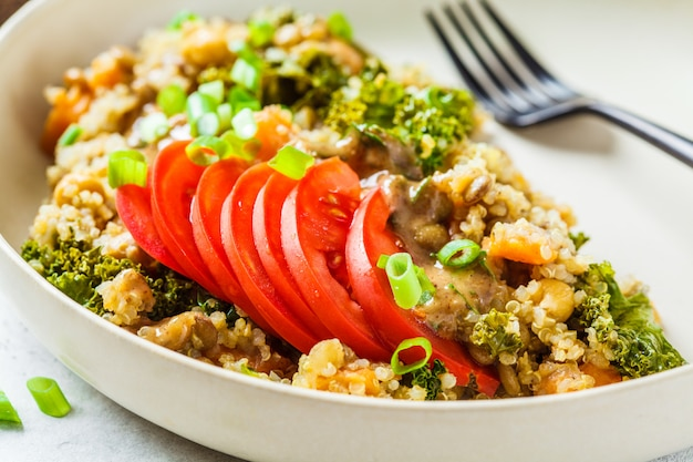 Stufato vegano con ceci, patate dolci e pomodoro fresco su un piatto bianco.