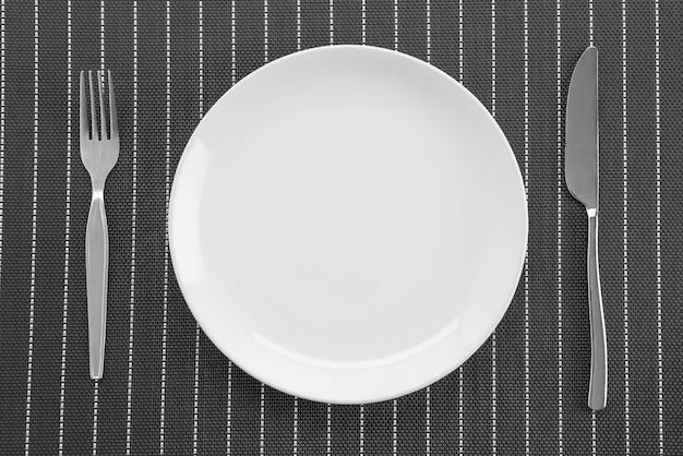 Stuoia a piastra con forchetta e coltello a piastra