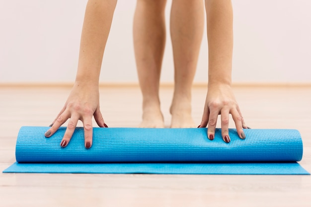 Stuoia di forma fisica di rotolamento della donna del primo piano dopo l'esercizio