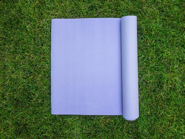 Stuoia viola di yoga sull'erba. tappetino per yoga, pilates o fitness