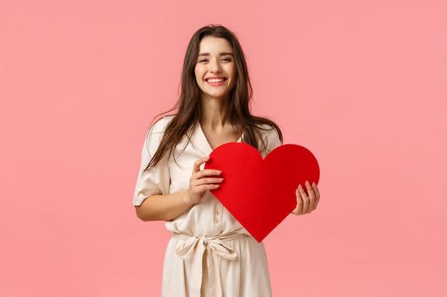 Stupida e spensierata, adorabile ragazza bruna seducente in costume, con in mano una grande carta rossa a cuore, con il miglior giorno di san valentino di sempre, sorridente e ridendo felice, in piedi rosa ottimista