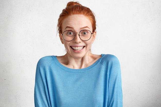 Stupita bellissima modella femminile felicissima con i capelli rossi e la pelle lentigginosa, indossa un maglione blu casual, guarda sorprendentemente attraverso gli occhiali rotondi