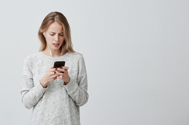 Stupita donna insoddisfatta con i capelli biondi tinti vestita casualmente con le cuffie bianche che tengono il messaggio di ricezione dello smartphone che è scioccato nel dimenticare un importante incontro con i businesspartners