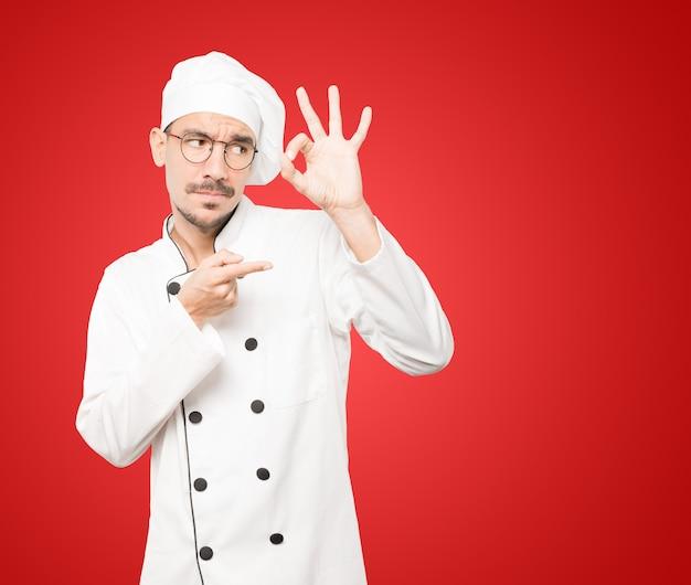 Stupito giovane chef che usa le mani come un binocolo