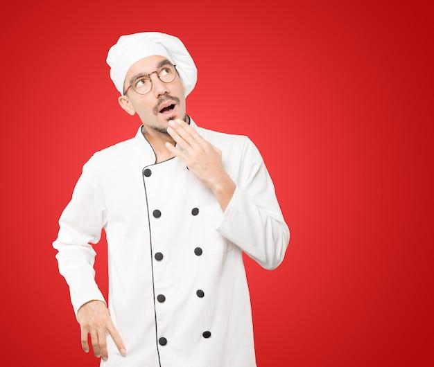 Stupito giovane chef con un gesto di shock