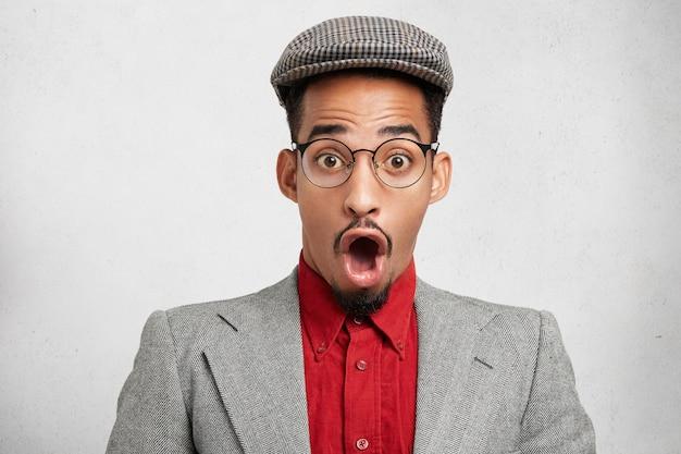 Stupito ragazzo hipster dalla pelle scura indossa berretto e giacca vecchio stile, apre la bocca in totale sorpresa,