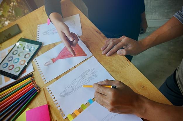 Stylish fashion designer lavora come schizzo di una nuova collezione in atelier. concetto di design creativo