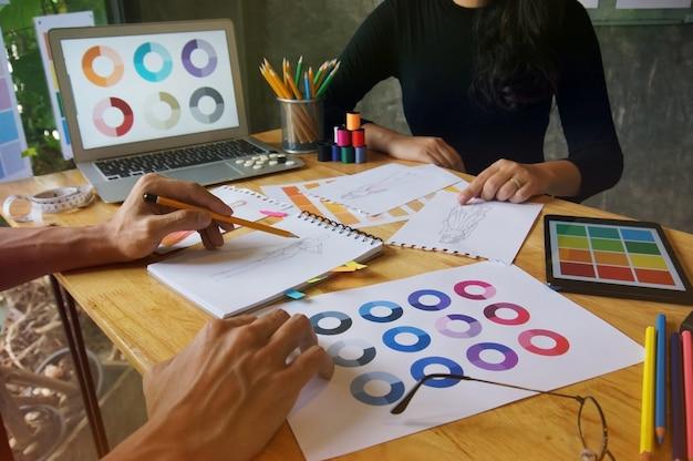 Stylish fashion designer lavora come schizzo di una nuova collezione in atelier. concetto di design creativo.