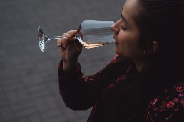 Stylish young girl beve vino in una caffetteria in una terrazza estiva. una ragazza con i capelli lunghi gode di un bicchiere di vino in una serata estiva. ritratto. avvicinamento