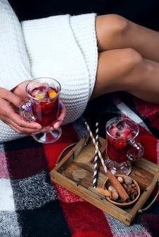 Su un letto un vassoio di legno con vin brulè ragazza con in mano un bicchiere con vin brulè a casa di natale