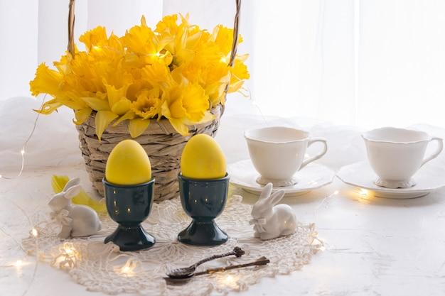 Su un tavolo bianco uova gialle, narcisi in un cestino, due tazze e figurine a forma di coniglio