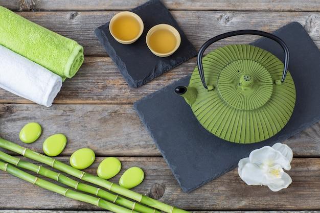 Su un tavolo di legno, bambù, asciugamani, orchidea, tè in ciotole e una teiera - sfondo della spa