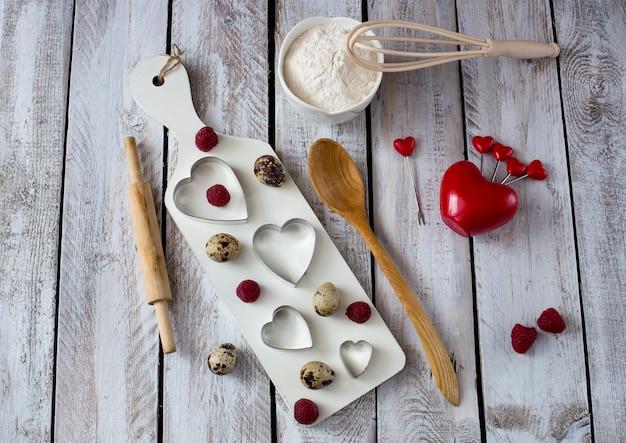 Su un tavolo di legno bianco forme di cottura a forma di cuori, uova, farina e lamponi
