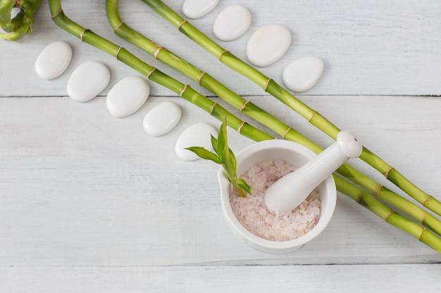 Su un tavolo di legno bianco, rami di bambù, sale marino e pietre bianche (spa)