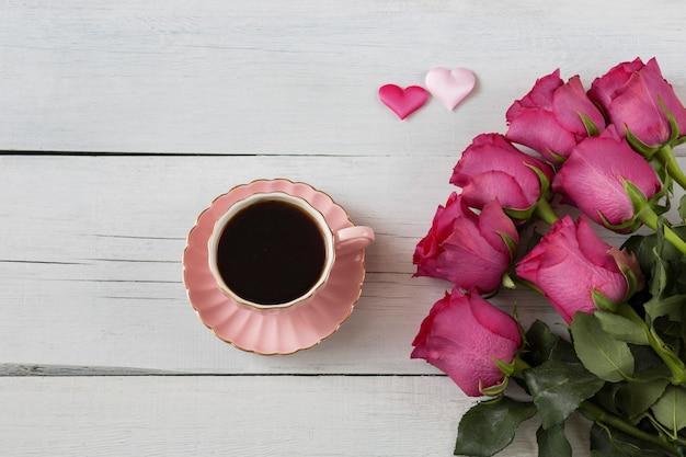 Su un tavolo di legno bianco rose rosa e caffè in una tazza rosa e due cuori rosa di sati