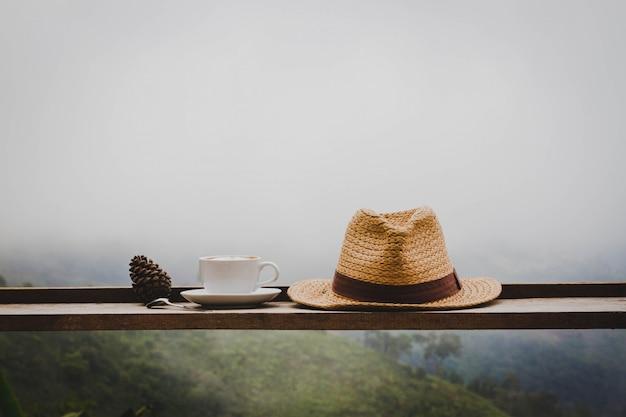 Su un tavolo di legno, c'è una tazza di caffè caldo e un cappello messo nel deserto.