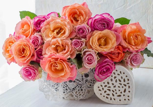 Su un tavolo luminoso un mazzo di rose con rose arancioni in un cestino bianco e una ceramica bianca