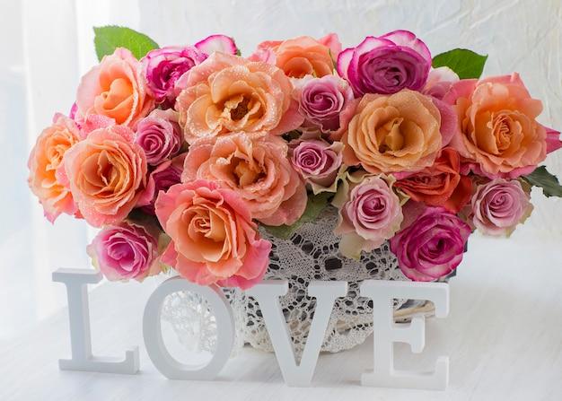 Su un tavolo luminoso un mazzo di rose con rose arancioni in un cestino bianco e uno di legno bianco