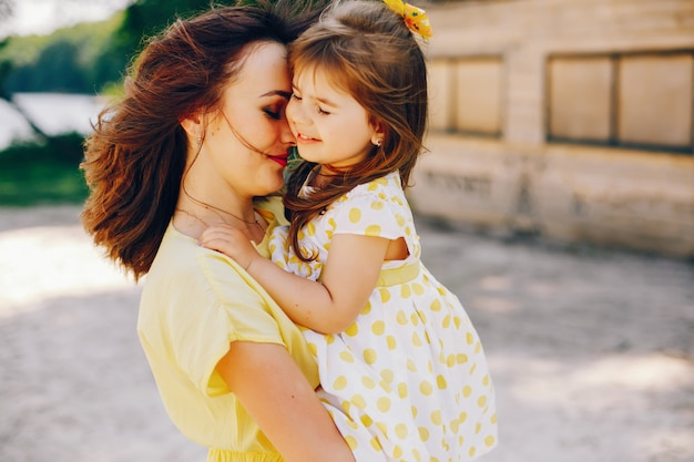 Su una spiaggia assolata con sabbia gialla, la mamma cammina in un vestito giallo e la sua piccola ragazza carina