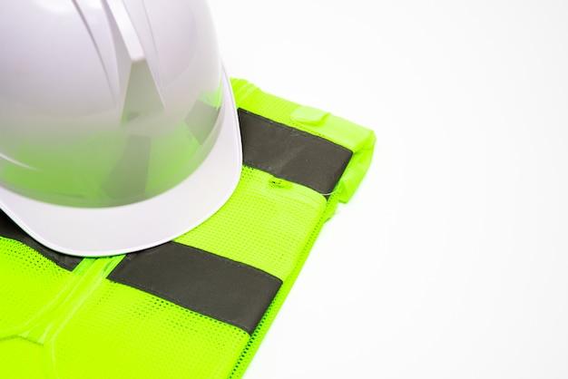 Su uno sfondo bianco, c'è un cappello di sicurezza e abiti da lavoro. con spazio di copia.