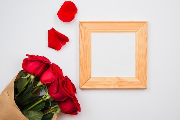 Su uno sfondo bianco ci sono bellissime rose rosse e una cornice. posto per testo, copia spazio