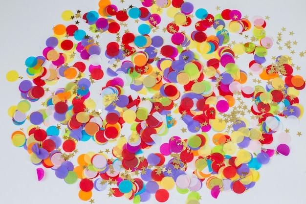 Su uno sfondo bianco coriandoli colorati e stelle dorate