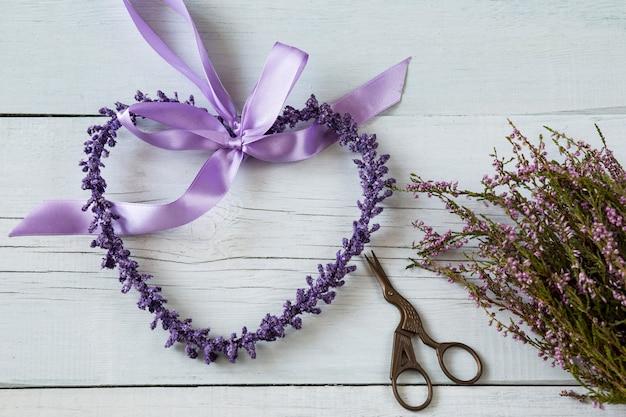 Su uno sfondo bianco in legno cuore viola fatto di fiori viola, forbici