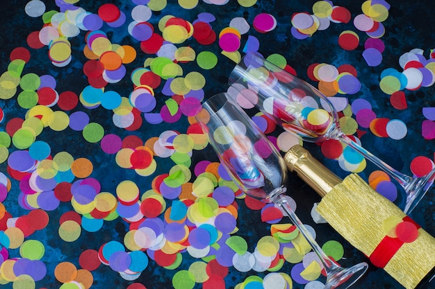 Su uno sfondo blu due bicchieri di champagne, una bottiglia di champagne e coriandoli luminosi