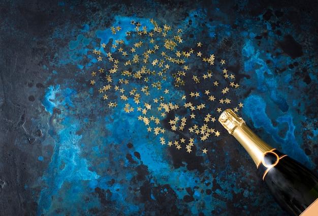 Su uno sfondo blu scuro una bottiglia di champagne e stelle dorate
