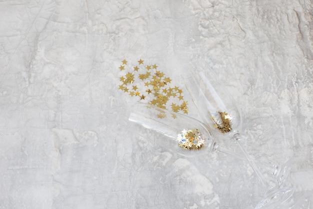 Su uno sfondo chiaro, due bicchieri di champagne e stelle dorate