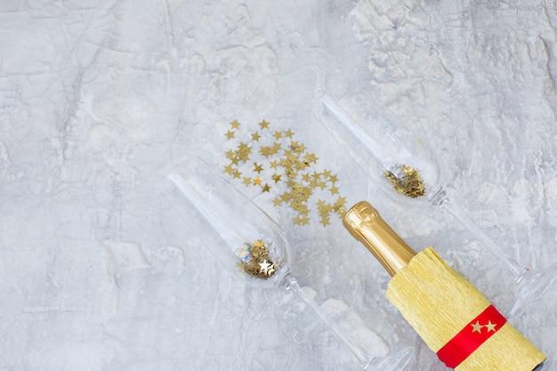 Su uno sfondo chiaro, due bicchieri di champagne, una bottiglia di champagne e stelle dorate