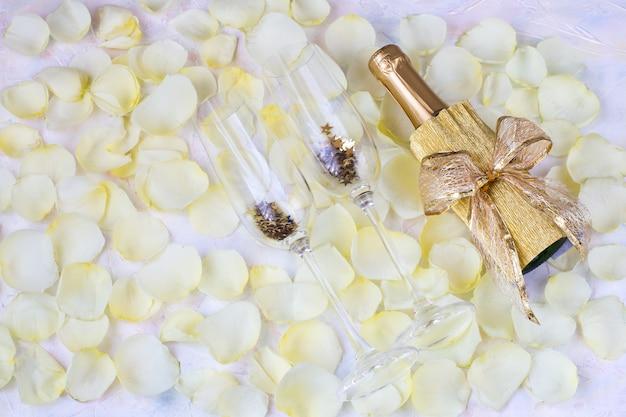 Su uno sfondo chiaro, petali di rosa bianca e due bicchieri per lo champagne, una bottiglia di champagne