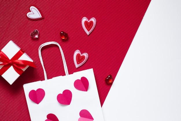 Su uno sfondo cremisi e bianco, una confezione regalo con un fiocco rosa, un sacchetto di carta bianco, cuori di cuori di vetro cremisi