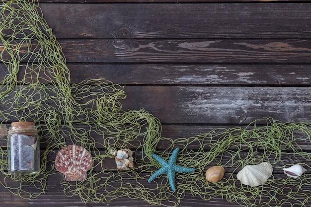 Su uno sfondo di legno attributi marini: rete, conchiglie, stelle marine, bottiglia con un messaggio