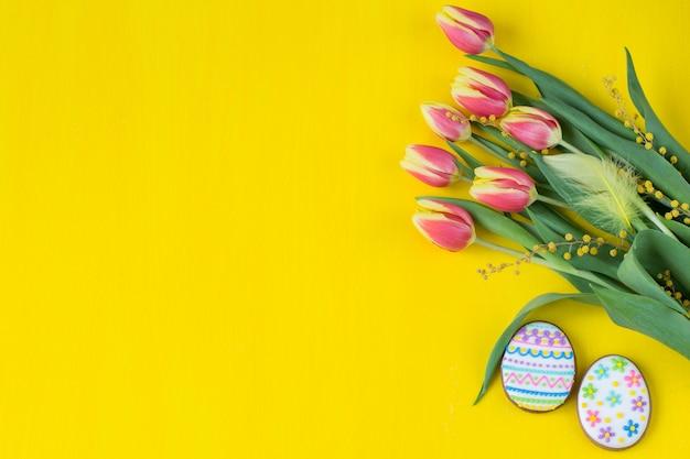 Su uno sfondo giallo tulipani, mimosa, piume e due pan di zenzero sotto forma di uova di pasqua