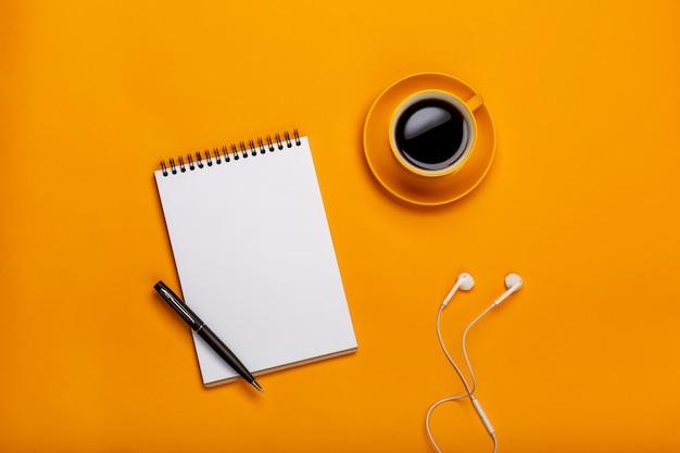 Su uno sfondo giallo, una tazza di caffè nero con un blocco note e cuffie