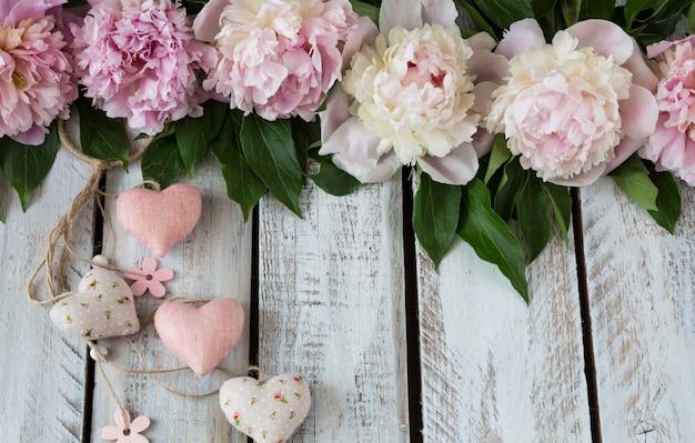 Su uno sfondo in legno chiaro peonie e cuori rosa