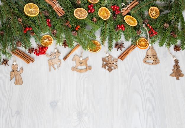 Su uno sfondo in legno chiaro, rami di pino, decorazioni e giocattoli in legno fatti a mano
