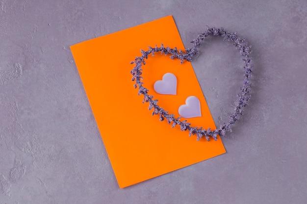 Su uno sfondo lilla, un foglio di carta arancione, due cuori di raso e un cuore di lavanda