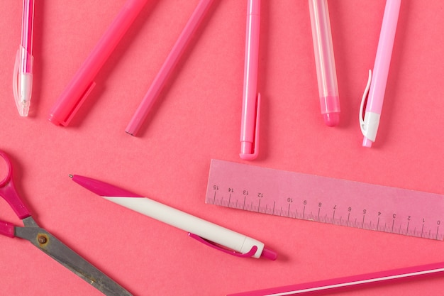 Su uno sfondo rosa, accessori per la scuola e una penna, matite colorate