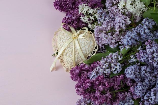 Su uno sfondo rosa un bouquet di lillà multicolore e un cuore di pizzo lavorato a maglia